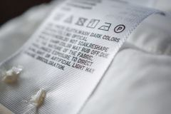 Cloth label tag with laundry care instructions. Close up stock photography
