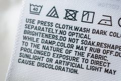 Cloth label tag with laundry care instructions. Close up stock image