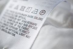 Cloth label tag with laundry care instructions. Close up stock photos