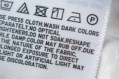 Cloth label tag with laundry care instructions. Close up royalty free stock images