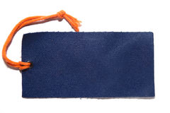 Cloth label with thread on white. Denim cloth label with orange thread on white with visible shadow stock image