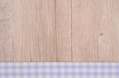Cloth with light blue checks on wooden background Royalty Free Stock Photography