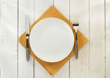 Cloth napkin and plate on wood. En background Royalty Free Stock Image