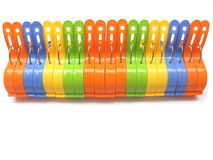 Cloth Pegs. 20 numbers of colorful cloth pegs in a line isolated on white background Stock Photo