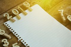 Cloth pin with number of year 2018 and a piece of blank paper. Copy space for text or logo.Sun flare.  royalty free stock images