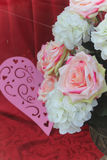 Cloth roses. Pink heart and white and pink cloth roses with a red background Stock Photos
