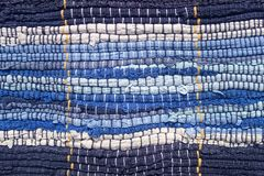 Cloth sewn from strips of fabric. Needlework, reuse of materials. Blue strips in a marine style. Textile background royalty free stock photos