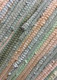 Cloth sewn from strips of fabric. Needlework, reuse of materials. Textile background. Stock Photos