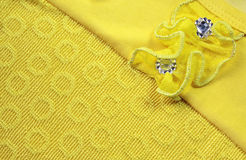 Cloth with  stitched  flower. Yellow satin textured cloth with  stitched  flower background Stock Image