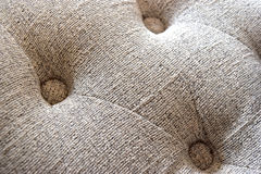 Cloth. Surface brown cloth with pins, buttons of the seat Royalty Free Stock Photos