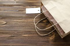 Cloth with tag in paper bag on wooden table.  Stock Image