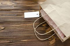 Cloth with tag in paper bag on wooden table.  Stock Photo