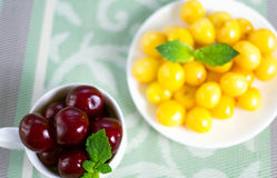 On a cloth there is a saucer and a cup with sweet cherries. Royalty Free Stock Photos