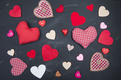 Cloth, wood and paper hearts on rustic wooden table. Royalty Free Stock Images