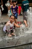Clothed children play at water fountain Stock Photography