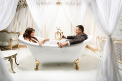 Clothed man and woman having fun in luxurious bath Royalty Free Stock Photography