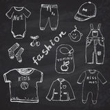 Clothes for baby boy set hand drawn sketch, on chalkboard background Royalty Free Stock Photos