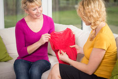 Clothes for baby. Young pregnant women holding the clothes for baby stock images