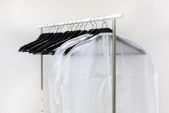 Clothes bags and hangers are on rack Stock Images
