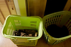 Clothes basket. Green baskets contain clothes for washing with low lighting Royalty Free Stock Photos