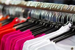 Clothes blouses and sweaters on hangers. In fashion boutique royalty free stock photography