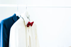 Clothes. Close-up of men`s classic white shirt with a red bow tie and a suit on a hanger Royalty Free Stock Photography