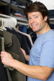 Clothes in closet. Man looking through shirts in his closet royalty free stock photos