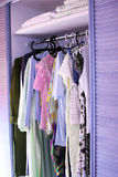 Clothes in closet. Clothes with hangers in closet vertical picture stock photo