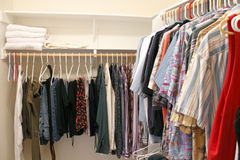 Clothes in a Closet. Mens wardrobe variety of pants and shirts clothing hung on plastic hangers in a home walk in closet. There are also a few bath towels on a royalty free stock photography