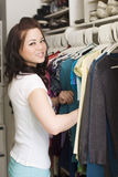 Clothes in closet. Woman looking at clothes in a closet royalty free stock photography