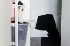 Clothes in closet drawer basket organizers, with bathroom in the background, and black towel hanging over bath tub. Closet drawer basket organizers, with stock image