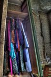Clothes in closet of old house. Colorful clothing hanging in closet inside old farmhouse Royalty Free Stock Photo