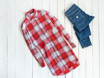 Clothes concept. Red and white checkered shirt and jeans on a wooden background. Top view.  royalty free stock image