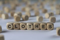 Clothes - cube with letters, sign with wooden cubes. Clothes - wooden cubes with the inscription `cube with letters, sign with wooden cubes`. This image belongs Stock Image