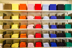 Clothes in the department store. Multi-colored folded T-shirts in the department store Royalty Free Stock Images