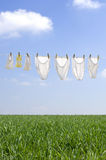 Clothes drying. In the summer breeze on clear blue sky with soft clouds Stock Photography