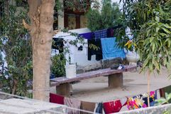 Clothes drying in a barren courtyard with bench and trees. Clothes drying in the middle of a huge courtyard with a bench and trees all around. Shows the huge Royalty Free Stock Photos