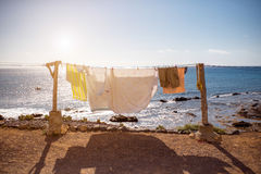 Clothes drying on the sea coast. Old clothes and sheets drying on the sea coast at the sunny weather Stock Images
