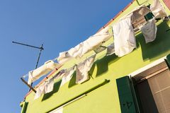 Clothes drying under the Italian sun, Venice, Italy. An old fishermen village called Burano, next to Venice, has its houses traditionally painted in bright stock photo