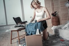 Slim young woman packing clothes of ex boyfriend into boxes stock images