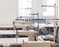 Clothes factory inside. Workplaces with modern sewing machines Stock Images