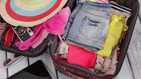 Clothes is filling suitcase up. Tablet and camera near suitcase. Explore new horizons. It's time for a journey stock footage