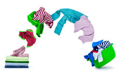 Clothes fly out of pile and fall on wash bowl Royalty Free Stock Photos