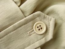 Clothes fragment. Unbleached linen clothes fragment with button Royalty Free Stock Images