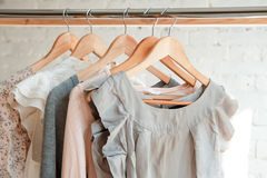 Clothes hang on clothing rack. Female clothes on clothing rack. Pastel colors Stock Photo