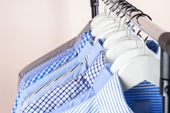 Cloth Hangers with Shirts. Men`s clothes. Clothes hang on a shelf . Cloth Hangers with Shirts. Men`s business clothes. Fashion Royalty Free Stock Images