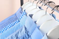 Cloth Hangers with Shirts. Men`s clothes. Clothes hang on a shelf . Cloth Hangers with Shirts. Men`s business clothes. Fashion Royalty Free Stock Image