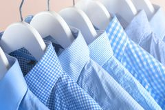 Cloth Hangers with Shirts. Men`s clothes. Clothes hang on a shelf . Cloth Hangers with Shirts. Men`s business clothes. Fashion Stock Photography