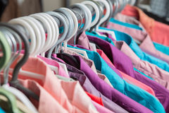 Clothes hang on a shelf in a designer clothes store Stock Photography