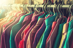 Clothes hang on a shelf in a designer clothes store Stock Images